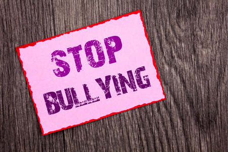 Foto de Handwriting Announcement text showing Stop Bullying. Conceptual photo Awareness Problem About Violence Abuse Bully Problem written Pink Sticky Note Paper the wooden background. - Imagen libre de derechos