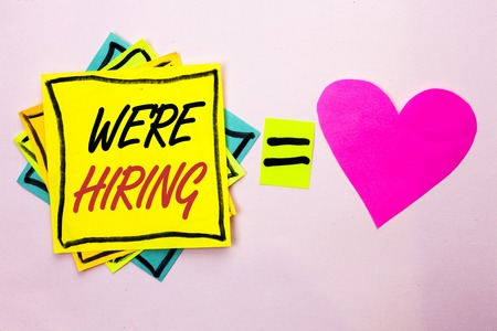 Photo for Text sign showing We're Hiring. Conceptual photo Recruiting Hiring Now Recruitment Vacancy Announced Hire written Yellow Sticky Note Paper the plain background Pink Heart next to it. - Royalty Free Image
