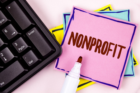 Foto de Text sign showing Nonprofit. Conceptual photo Activities that do not generate revenues to the executor written Pink Sticky Note paper plain background Marker and Black Keyboard. - Imagen libre de derechos