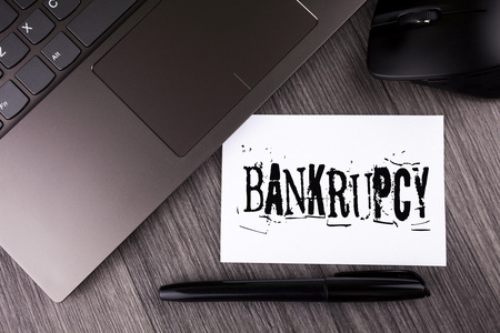 Foto de Writing note showing  Bankrupcy. Business photo showcasing Company under financial crisis goes bankrupt with declining sales written Sticky Note Paper the wooden background Laptop Mouse Pen - Imagen libre de derechos
