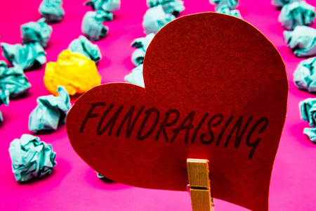 Photo for Handwriting text Fundraising. Concept meaning Seeking of financial support for charity cause or enterprise Clothespin holding red heart paper crumpled papers ideas mistakes trials - Royalty Free Image