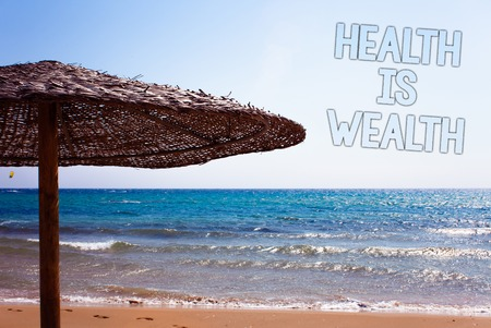 Foto de Writing note showing  Health Is Wealth. Business photo showcasing being in good shape great value Stay healthy eat Healthy Blue beach sand message idea sunshade water sky natural landscape - Imagen libre de derechos