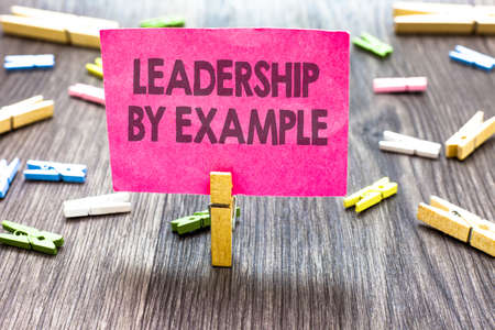 Photo for Writing note showing Leadership By Example. Business photo showcasing Becoming role model for people Have great qualities Multiple clips woody table small card clipped notice announcement - Royalty Free Image