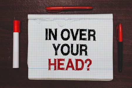 Photo for Handwriting text writing In Over Your Head question. Concept meaning To be involved in a difficult situation problem Written black, red words notepad on brown stage white highlighter red pens - Royalty Free Image
