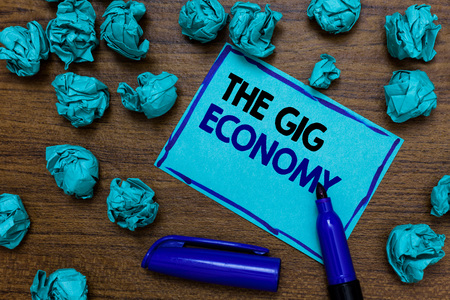 Photo pour Conceptual hand writing showing The Gig Economy. Business photo showcasing Market of Short-term contracts freelance work temporary written blue letters on page blue marker and paper lumps - image libre de droit