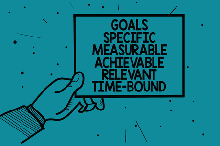 Photo pour Writing note showing Goals Specific Measurable Achievable Relevant Time Bound. Business photo showcasing Strategy Mission Man hand holding paper communicating dotted turquoise background - image libre de droit