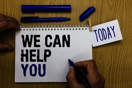 Foto de Handwriting text We Can Help You. Concept meaning Support Assistance Offering Customer Service Attention Man holding marker notebook clothespin reminder wooden table cup coffee - Imagen libre de derechos