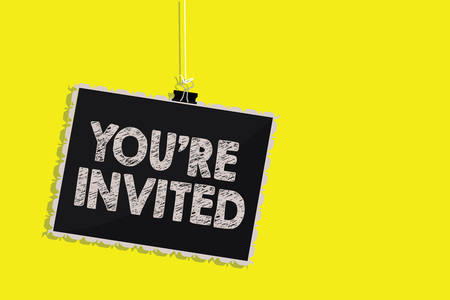 Photo for Writing note showing You re are Invited. Business photo showcasing Please join us in our celebration Welcome Be a guest Hanging blackboard message communication sign yellow background - Royalty Free Image