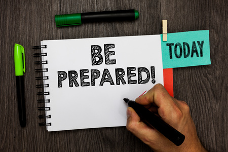 Foto de Conceptual hand writing showing Be Prepared. Business photo showcasing Getting ready for whatever will happen Plan Ahead of time Man holding marker notebook reminder cup markers wood table - Imagen libre de derechos