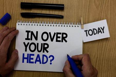 Photo for Word writing text In Over Your Head question. Business concept for To be involved in a difficult situation problem Hand hold pen notepad with words paperclip grip note paper woody base black pen - Royalty Free Image