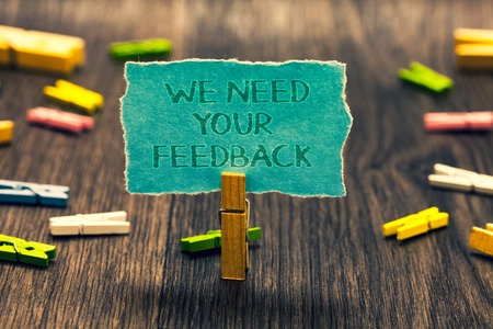 Foto de Conceptual hand writing showing We Need Your Feedback. Business photo showcasing Give us your review thoughts comments what to improve Paperclip retain blue cardboard blurry woody desk paper clip - Imagen libre de derechos