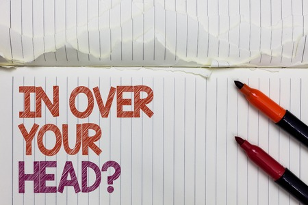 Photo for Text sign showing In Over Your Head question. Conceptual photo To be involved in a difficult situation problem White torn page written some letters beside laid two red marker - Royalty Free Image