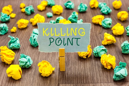 Foto de Text sign showing Killing Point. Conceptual photo Phase End Review Stage Gate Project Evaluation No Go Clothespin holding gray note paper crumpled papers several tries mistakes - Imagen libre de derechos