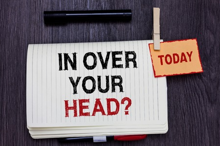Photo for Handwriting text writing In Over Your Head question. Concept meaning To be involved in a difficult situation problem Written paper on wooden desk paper clip grip note with red words black pen - Royalty Free Image