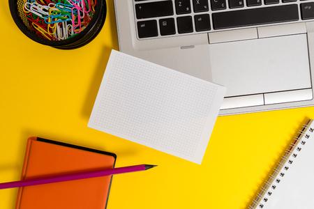 Foto de Laptop pencil sheet clips container spiral notebook colored background - Imagen libre de derechos