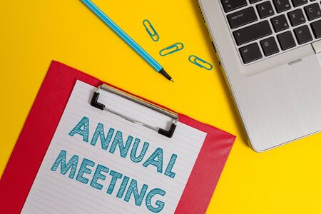 Foto de Word writing text Annual Meeting. Business photo showcasing Yearly gathering of an organization interested shareholders Open laptop clipboard blank paper sheet marker clips colored background - Imagen libre de derechos