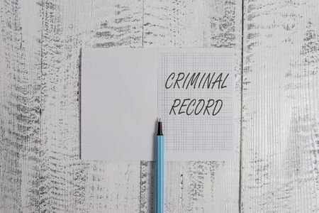 Foto de Conceptual hand writing showing Criminal Record. Concept meaning profile of a demonstrating criminal history with details Square notebook fine highlighter lying on wooden background - Imagen libre de derechos