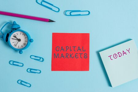 Photo pour Writing note showing Capital Markets. Business concept for Allow businesses to raise funds by providing market security Alarm clock wakeup clips notepad sticky note pencil colored background - image libre de droit