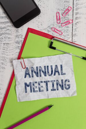 Foto per Handwriting text Annual Meeting. Conceptual photo Yearly gathering of an organization interested shareholders Clipboard paper sheet pencil smartphone note clips wooden retro background - Immagine Royalty Free