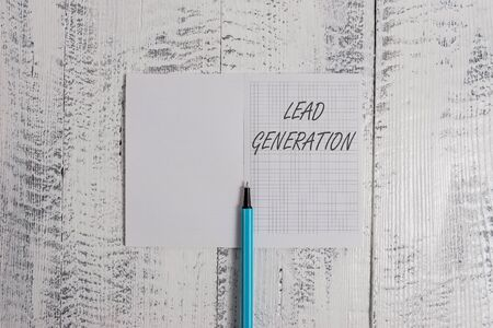 Foto de Conceptual hand writing showing Lead Generation. Concept meaning initiation of consumer interest or enquiry into products Square notebook fine highlighter lying on wooden background - Imagen libre de derechos