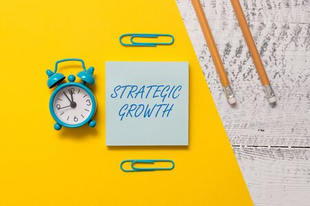 Photo pour Text sign showing Strategic Growth. Business photo text create plan or schedule to increase stocks or improvement Notepad clips colored paper sheet markers alarm clock wooden background - image libre de droit