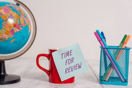 Photo pour Writing note showing Time For Review. Business concept for review of a system or situation in its formal examination Globe map world earth coffee cup sticky note pens holder wooden table - image libre de droit