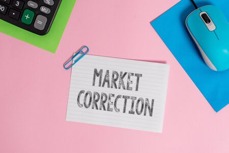 Foto de Conceptual hand writing showing Market Correction. Concept meaning When prices fall 10 percent from the 52 week high Wire electronic mouse calculator paper colored background - Imagen libre de derechos