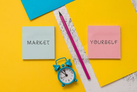 Photo pour Text sign showing Market Yourself. Business photo text Making yourself for any kind of task and project in life Notepads marker pen colored paper sheets alarm clock wooden background - image libre de droit
