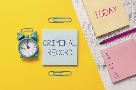 Photo pour Handwriting text writing Criminal Record. Conceptual photo profile of a demonstrating criminal history with details Notepads clips colored paper sheet marker alarm clock wooden background - image libre de droit