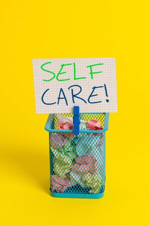 Photo pour Text sign showing Self Care. Business photo showcasing practice of taking action to preserve or improve ones own health Trash bin crumpled paper clothespin empty reminder office supplies yellow - image libre de droit