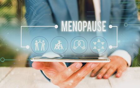 Foto de Word writing text Menopause. Business photo showcasing Period of peranalysisent cessation or end of menstruation cycle Male human wear formal work suit presenting presentation using smart device - Imagen libre de derechos