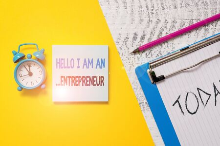 Photo for Writing note showing Hello I Am An Entrepreneur. Business concept for demonstrating who sets up a business or startups Notepad clipboard colored paper sheet alarm clock wooden background - Royalty Free Image
