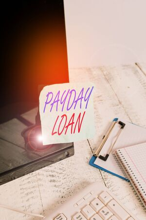 Photo pour Conceptual hand writing showing Payday Loan. Concept meaning Something lent or furnished on condition being returned Note paper taped to black screen near keyboard stationary - image libre de droit