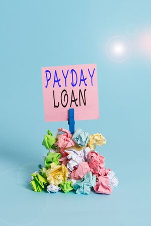 Photo pour Text sign showing Payday Loan. Business photo showcasing Something lent or furnished on condition being returned Reminder pile colored crumpled paper clothespin reminder blue background - image libre de droit