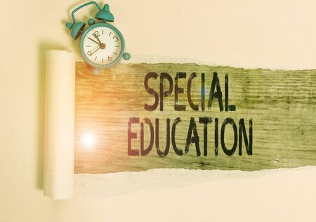 Foto de Text sign showing Special Education. Business photo showcasing form of learning given to students with mental challenges Alarm clock and torn cardboard placed above a wooden classic table backdrop - Imagen libre de derechos