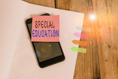 Foto de Word writing text Special Education. Business photo showcasing form of learning given to students with mental challenges Note book four arrow banners smartphone sticky note old wooden background - Imagen libre de derechos