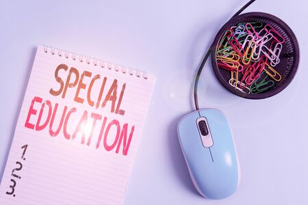 Foto de Word writing text Special Education. Business photo showcasing form of learning given to students with mental challenges Blank notebook and clips with computer mouse placed above pastel backdrop - Imagen libre de derechos