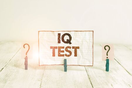 Foto de Handwriting text Iq Test. Conceptual photo attempt to measure your cognitive ability huanalysis intelligence Scribbled and crumbling sheet with paper clips placed on the wooden table - Imagen libre de derechos