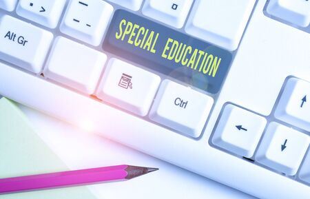 Foto de Conceptual hand writing showing Special Education. Concept meaning form of learning given to students with mental challenges White pc keyboard with note paper above the white background - Imagen libre de derechos