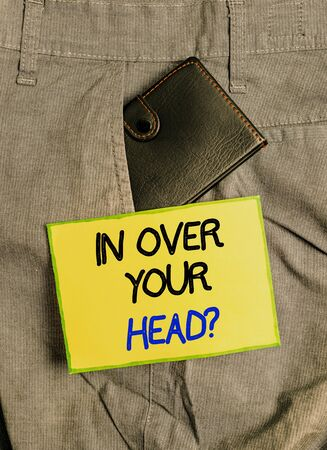Photo for Handwriting text writing In Over Your Head question. Conceptual photo To be involved in a difficult situation problem Small little wallet inside man trousers front pocket near notation paper - Royalty Free Image