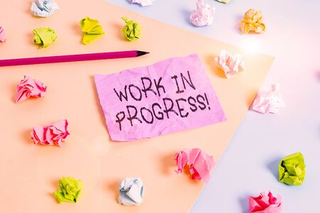 Foto de Writing note showing Work In Progress. Business concept for unfinished project that still added to or developed Colored crumpled papers empty reminder blue yellow clothespin - Imagen libre de derechos