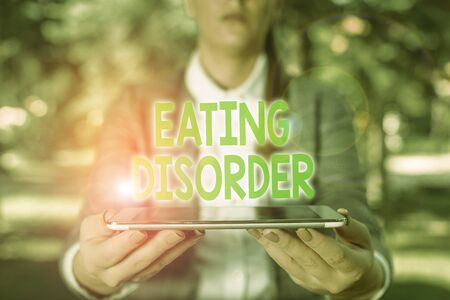 Photo for Writing note showing Eating Disorder. Business concept for illnesses that are characterized by irregular eating habits Outdoor scene with business woman holds lap top with touch screen - Royalty Free Image