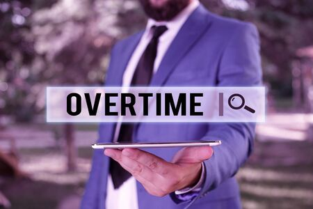 Photo for Word writing text Overtime. Business photo showcasing Time or hours worked in addition to regular working hours Businessman in blue suite stands with mobile phone in hands - Royalty Free Image