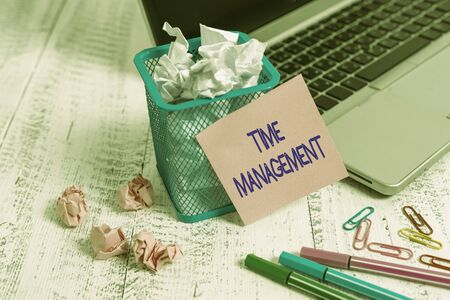 Photo pour Word writing text Time Management. Business photo showcasing the ability to use one time effectively or productively Laptop sticky note waste basket crushed paper ball clips pens vintage table - image libre de droit