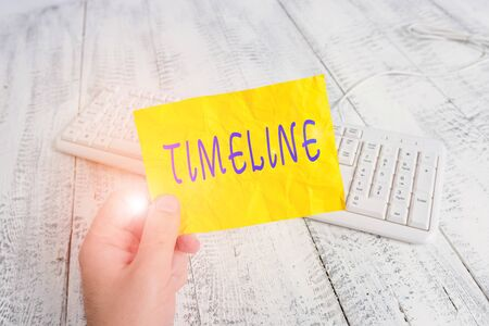 Foto de Text sign showing Timeline. Business photo showcasing graphical representation of period time on which events are marked man holding colorful reminder square shaped paper white keyboard wood floor - Imagen libre de derechos