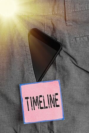 Foto de Conceptual hand writing showing Timeline. Concept meaning graphical representation of period time on which events are marked Smartphone device inside trousers front pocket note paper - Imagen libre de derechos