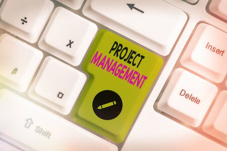 Foto de Conceptual hand writing showing Project Management. Concept meaning practice of the work of a team to achieve specific goals White pc keyboard with empty note paper above white key copy space - Imagen libre de derechos