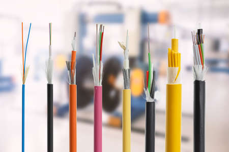 Photo pour Collection of fiber optical cables on blurry production room background. Loose tubes with optical fibres and central strenght member, waterblocking glass yarn and ripcord, multimode or single mode - image libre de droit