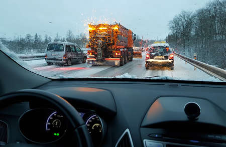Photo pour snowstorm, poor car driving on slick roads and lots of traffic, snow plow doing snow removal during blizzard - image libre de droit