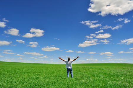 Photo pour man with arms raised on a green field under beautiful sky - image libre de droit